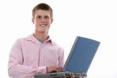 Menino atrativo dos anos de idade dezesseis com computador portátil Fotos de Stock Royalty Free