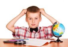 Menino aturdido que senta-se na tabela no caderno, lápis, globo Fotos de Stock Royalty Free