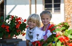 Menino bávaro feliz com a irmã na exploração agrícola em Alemanha Foto de Stock Royalty Free