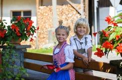 Menino bávaro feliz com a irmã na exploração agrícola em Alemanha Fotografia de Stock