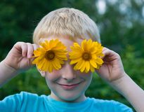 Menino bonito com as flores nos olhos que têm o divertimento fotos de stock royalty free