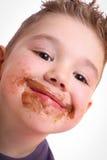 Menino bonito com o chocolate manchado Imagem de Stock