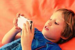 Menino bonito com telefone móvel Fotos de Stock