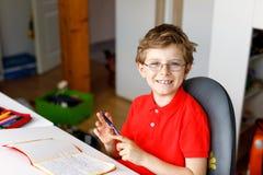 Menino bonito da criança com os vidros em casa que fazem os trabalhos de casa, escrevendo letras com penas coloridas Imagem de Stock Royalty Free