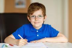 Menino bonito da criança com os vidros em casa que fazem os trabalhos de casa, escrevendo letras com penas coloridas Imagens de Stock