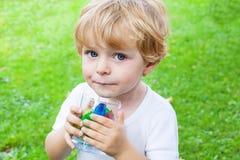 Menino bonito da criança com vidro de cubos de gelo da baga Imagens de Stock