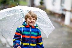 Menino bonito da criança na maneira à escola que anda durante o granizo, a chuva e a neve com um guarda-chuva no dia frio Feliz e fotografia de stock