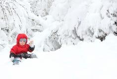 Menino bonito da criança no terno do inverno que senta-se em um monte de neve grande e em aumentos sua mão no cumprimento, cercad fotos de stock royalty free