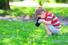 Menino bonito da criança que fotografa flores Imagens de Stock Royalty Free