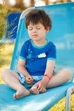 Menino bonito da criança que senta-se no sunbed Fotos de Stock Royalty Free