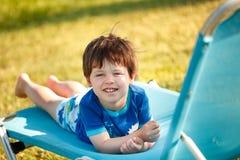 Menino bonito da criança que senta-se no sunbed Fotos de Stock