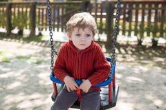 Menino bonito da criança que tem o divertimento no balanço Foto de Stock Royalty Free