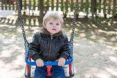 Menino bonito da criança que tem o divertimento no balanço Foto de Stock