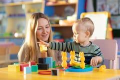 Menino bonito da mulher e da criança que joga brinquedos educacionais no jardim de infância ou na sala do berçário fotografia de stock royalty free
