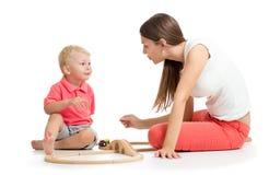 Menino bonito da mulher e da criança que joga brinquedos da estrada de ferro em casa fotografia de stock