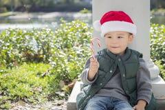 Menino bonito da raça misturada com o bastão de doces que veste Santa Hat Imagem de Stock