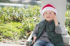 Menino bonito da raça misturada que veste Santa Hat com bastão de doces Foto de Stock