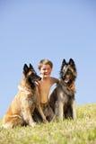 Menino bonito de sorriso com os dois pastores belgas Fotografia de Stock