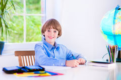 Menino bonito de sorriso que faz trabalhos de casa Fotografia de Stock Royalty Free