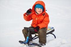 Menino bonito de sorriso que senta-se em seu 'trotinette' da neve Fotos de Stock Royalty Free