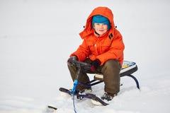Menino bonito de sorriso que senta-se em seu 'trotinette' da neve Imagem de Stock Royalty Free