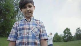 Menino bonito do retrato que olha na posição da câmera no primeiro plano quando seu paizinho ou irmão mais idoso que jogam com bo filme