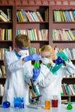 Menino bonito e menina que fazem a pesquisa da bioquímica na classe de química fotos de stock royalty free
