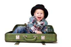 Menino bonito em um chapéu que senta-se em uma mala de viagem Imagem de Stock