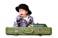 Menino bonito em um chapéu que senta-se em uma mala de viagem Fotografia de Stock