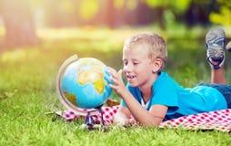 Menino bonito em um parque com um globo foto de stock