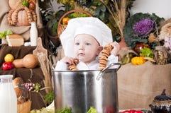 Menino bonito em uma bandeja do cozinheiro Imagens de Stock Royalty Free