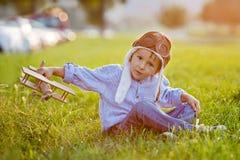 Menino bonito, jogando com o avião no por do sol no parque Foto de Stock Royalty Free