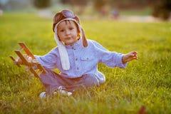 Menino bonito, jogando com o avião no por do sol no parque Fotografia de Stock