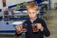 Menino bonito na cantina da escola o estudante da escola primária remove os pratos Foto de Stock