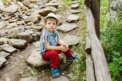 Menino bonito no chapéu e nas calças vermelhas que sentam-se em um trajeto de pedra no parque no verão Fotografia de Stock Royalty Free