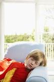 Menino bonito no traje do super-herói que dorme na poltrona Imagem de Stock