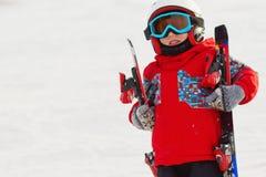 Menino bonito pequeno com esquis e um equipamento do esqui Esquiador pequeno no Foto de Stock