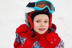 Menino bonito pequeno com esquis e um equipamento do esqui Esquiador pequeno no Imagem de Stock Royalty Free