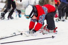 Menino bonito pequeno com esquis e um equipamento do esqui Esquiador pequeno no Imagens de Stock