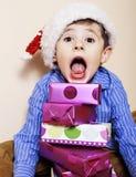 Menino bonito pequeno com presentes do Natal em casa feche acima de emocional foto de stock