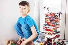 Menino bonito pequeno da crian?a em idade pr?-escolar que joga o sorriso feliz dos brinquedos do construtor em casa, fim do conce imagens de stock royalty free