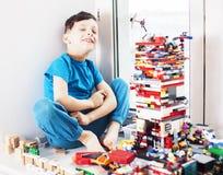 Menino bonito pequeno da crian?a em idade pr?-escolar que joga o sorriso feliz dos brinquedos do construtor em casa, fim do conce imagem de stock