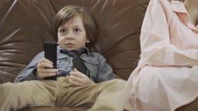 Menino bonito pequeno do retrato que senta-se no sofá de couro com os pés que mudam distante os canais na tevê usando o telecontr filme
