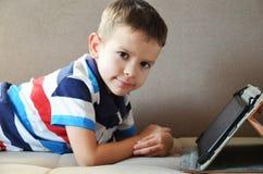Menino bonito pequeno em um t-shirt verde que joga jogos em uma tabuleta e que olha desenhos animados Criança com tabuleta foto de stock