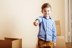 Menino bonito pequeno na sala vazia, remoove à casa nova as caixas sozinhas home do emong fecham-se acima da criança Imagens de Stock Royalty Free