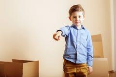 Menino bonito pequeno na sala vazia, remoove à casa nova as caixas sozinhas home do emong fecham-se acima da criança Fotografia de Stock