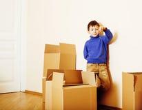 Menino bonito pequeno na sala vazia, remoove à casa nova as caixas sozinhas home do emong fecham-se acima do sorriso da criança Fotografia de Stock