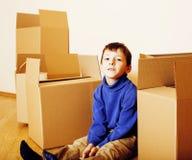 Menino bonito pequeno na sala vazia, remoove à casa nova as caixas sozinhas home do emong fecham-se acima do sorriso da criança Imagens de Stock Royalty Free