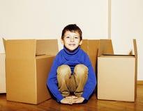 Menino bonito pequeno na sala vazia, remoove à casa nova as caixas sozinhas home do emong fecham-se acima do sorriso da criança Fotografia de Stock Royalty Free