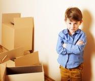 Menino bonito pequeno na sala vazia, remoove à casa nova sozinhos home, foto de stock royalty free